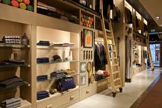 Store design/merchandising in Woolrich store, London ... clean, organized and classy walls that could be used with a variety of free-standing merchandisers.