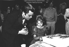 """Stephen King, Drew Barrymore, Bangor. Author Stephen King and child film star Drew Barrymore during the world premier of King's """"Fire-Starter"""" a film starring Barrymore. The premier was held in Bangor, King's hometown, to benefit COMBAT, a consumer organization. Item # 1503 on Maine Memory Network"""