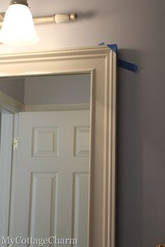 How to make builders grade mirrors pretty. For glue--she uses Loctite Power Grab (all-purpose instant grab) to glue the frame on the mirror. This is a perfect tutorial for how to make my HUGE bathroom mirror into a leaning wall mirror for my sewing room.