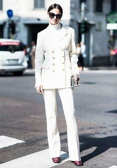 A turtleneck is worn with a double-breasted blazer, trousers, square-toe boots, a metallic bag, and black sunglasses