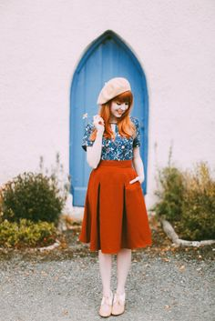 I like the lively contrast between the plain red skirt and blue shirt with its intricate floral print.