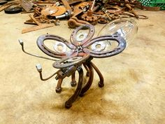 Firefly. Welding the sculpture up using vintage agricultural, or used farm equipment parts, and scrap metal. Rustic pieces welded together making yard art. The giant light bulb came from a barn mounted light.