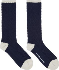 Tall wool knit socks in navy. Subtle cable knit pattern throughout. Toe, heel, and rib knit cuff in off-white. Logo printed at sole in white. Tonal stitching.