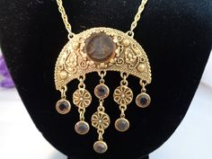 Vintage Goldette Fob Necklace with an Intaglio Cameo featured in the Center with Five Hanging Bezel Crystals and Goldtone Floral Charms. Stunning example of Goldette! Free Shipping to the U.S. + $1.00 Handling Fee.  Come to our store and see our fabulous Goldette collection.  www.CCCsVintageJewelry.com have a great vintage day! Best, Coco