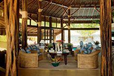 A interação desta morada com a natureza é inegável. Na construção nota-se a forte presença da madeira, que se encontra em pilares, esquadrias, no teto e no piso. Em algumas paredes, o uso de grandes pedras atribui ao espaço um charme rústico. Seguindo o clássico estilo de decoração praiana carioca, há a predominância de azul e branco por toda a casa. O responsável por esse projeto é o arquiteto Sig Bergamin.