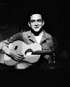 Johnny Cash holds his $10 guitar. He sold appliances door to door before auditioning for and signing with Sam Phillips at Sun Records in Memphis, Tenn.