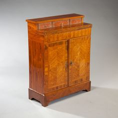 A FINE LOUIS XIV BUREAU CABINET : Nicholas Wells Antiques A fine 19th century Louis XIV rosewood bureau cabinet of unusually small proportions. The stepped upper section opening to a sliding writing surface with two sunken drawers and three leather fronted boxes. The lower section with cupboard doors opening to shelves. The cabinet is veneered in book matched rosewood with feather banding throughout.