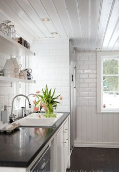 Great ceiling detail, open shelves, and subway tiles in this all white kitchen.