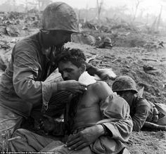 An American medic applies a field dressing to the neck of an injured soldier while another soldier in Tanapag, Saipan in June 1944. In the distance behind them, a soldier is visible in a foxhole