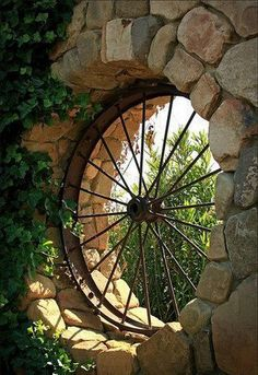Old iron metal wagon wheel repurposed into garden outdoor window; rustic farm style. http://theownerbuildernetwork.co/ideas-for-your-rooms/doors-and-windows-gallery/doors-and-windows  Upcycle, Recycle, Salvage, diy, thrift, flea, repurpose, refashion!  For vintage ideas and goods shop at Estate ReSale & ReDesign, Bonita Springs, FL