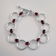 Garnet Circle Bracelet - Solid Silver hoops with 7 garnet cabouchons linking each circle to form a gorgeous chain. Jewelry Photography, Silver Hoops, Silver Bracelets, Garnet, Jewellery, Chain, Beautiful, Model, Silver Cuff Bracelets