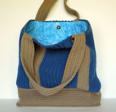 This hand crochet tote bag was made in Ocean Blue and Taupe (tan) and is partially lined with an aqua blue cotton fabric featuring dragonflies. The 4th photo shows that the bottom section of the bag is NOT lined. This tote bag features a magnetic snap closure and an interior pocket which measures approximately 6 by 6 inches (15.24 X 15.24 cm). The lining is completely hand sewn.  Bag measures 17 wide (43.18 cm), 15.5 tall (39.37 cm) and is 3.5 from front to back (8.89 cm) Made of 100%…