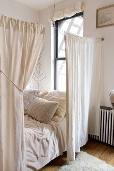 simple white curtains separate the comfy sleeping space making it more relaxing