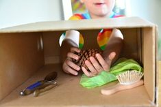Once I found the right sized box this activity took me less than five minutes to make. A cardboard box with two holes (for the chid's arms) = Montessori Mystery Box. This is a fun game that depending