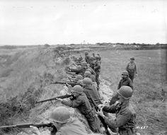 Dans un paysage de lande, une unité américaine tire en appui  contre un talus. Probablement dans le cadre d'un exercice.