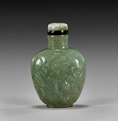 """Carved green jade snuff bottle; of spade form, with design to both sides of various florals in low relief; matching stopper; H: 2 3/8"""""""