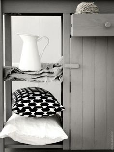 Det rejäla sidobordet OLOFSTORP ser ut att vara sprunget ur en klassisk arbetsbänk. På de öppna hyllorna: Sockerärt vas, NÄVIVA kudde och VITFJÄRIL kuddfodral.