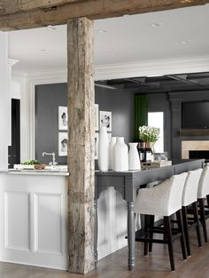 Love the combo here....Exposed wood beam mixed with a semi-contemporary bar/island against dark grey backround