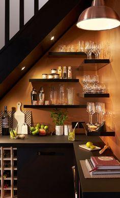 Des étagères installées sous l'escalier pour gagner de la place dans la cuisine
