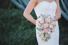 Soft hues of pink, orange and white roses fill this gorgeous bouquet. Wedding Photographer: Randy + Ashley.