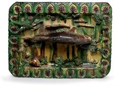 A FRENCH PALISSY STYLE FAIENCE TROMPE L'OEIL RECTANGULAR DISH  CIRCA 1865-750, ATTRIBUTED TO EMILE GAMBUT  Molded and applied with a large central fish and four smaller fish swimming among reeds and clusters of moss, a frog and shells at the periphery, the shaped rectangular rim molded with anthemion  19¾ x 14½ in. (50.1 x 36.7 cm.)