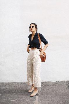 6 truques para se manter sempre estilosa. Camisa preta com nozinho na cintura, calça pantacourt branca, sandália transparente de plástico