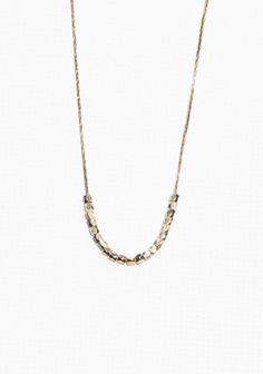 Free-moving faceted beads are set on a fine chain in this delicate, everyday necklace. Crafted from brass.