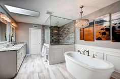 White panel molding wainscoting create depth and contrast to the cool tones of the gray walls. Photo by TGI HomeCrafters LLC