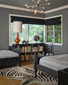 This boys' bedroom features a modern Sputnik light fixture and an orange, blue and black color scheme. The space is fun and lively yet functional for kids.
