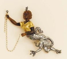 An Rare Antique Diamond And Agate Mythological Creature   The upper body of the agate negress holding a sceptre and seed pearl chain with diamond floral and gem-set mid-rif decoration and pavé-set old mine-cut diamond beast-like lower body, the reverse showing a carved scroll grill, mounted in silver and gold, (screw fitting for brooch on reverse), one hand showing significant repair, circa 1890