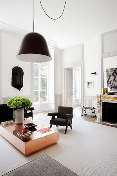 Living space with high ceilings, a modern pendant light, a rose gold coffee table, and a Pierre Jeanneret chair