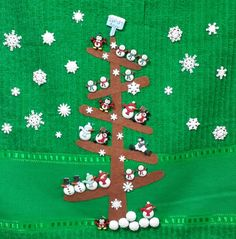 Una toalla con decoración navideña, un arbol llenito de muñecos de  nieve, ¡y todos son botones!
