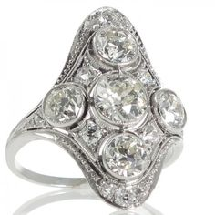An Art Deco platinum ring made as a rounded kite shaped plaque with a central old cut diamond of estimated weight 0.63ct with four diamonds spaced around in individual bezel mounts each divided by a small diamond and highlighted around the outer edges of the plaque with millegrained detail and a fine row of tapering diamonds at either end all tapering in at either side to a ribbed band. #RutherfordJewellery #Melbourne