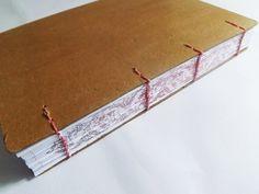 Caderno artesanal rústico com arabesco na lombada.