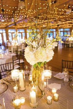 Tall white centerpiece with various shapes and sizes of candles, photo by Adam Sjöberg and Nathan Smith for Ira Lippke Studios | via junebugweddings.com