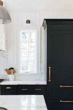 A bronze and white glass barn sconce is mounted to a white tongue and groove backsplash over a long window half framed by white marble.