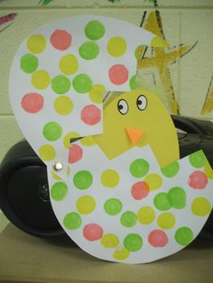 Bingo type Dabbers onto an egg shape. Cut the egg like it's cracked. Use a paper fastener to the edge to reveal an egg shaped chick inside. You can't tell, but there is a yellow feather sticking up on top of the chick's head. Sticker eyes and orange beak.