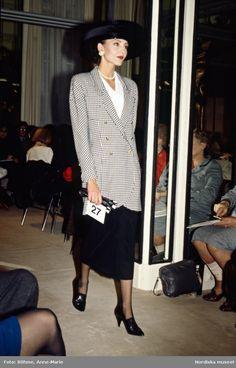 Modevisning. Modell i rutig kavaj, svart kjol och bredbrättad hatt. Från Chanel.
