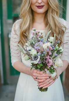 Brides.com: . A purple-and-white posy comprised of David Austin roses, anemones, dried lavender, scabiosa, wax flower, wild forget me nots, dried wheat, and spray roses, created by Battersea Flower Station.