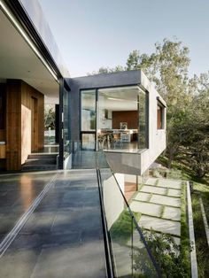 This expansive modern home, designed by Noah Walker, was built into a hillside to fully integrate with its natural surroundings. It features a gorgeous infinity pool and is surrounded by majestic oak trees.