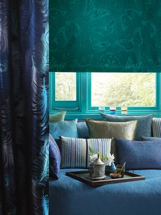 Matthew Williamson in collaboration with Osborne & Little. A home decorated in different shades of blue and green from the 2015 Cubana collection and a tray of drinks.
