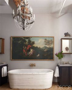 A vintage Italian chandelier hangs above an antique tub in this master bath of this Courtnay Daniels Haden-designed SoHo loft.