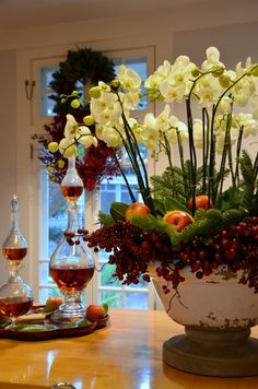 Beautiful holiday arrangement with greenery, apples, cranberries and orchids