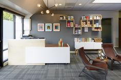 At JumpstartMD, a weight loss clinic, the reception area complements the patient waiting room, with artwork that suggests motion prominently displayed. Interior design by Urban Chalet.
