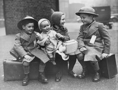 26th October 1940: Three young evacuees sit on their suitcases ready for their journey away from the danger of the city. (Photo by Reg Speller/Fox Photos/Getty Images)