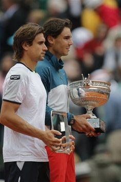 Spain's Rafael Nadal, right, holds the trophy after winning against compatriot David Ferrer, left, in three sets 6-3, 6-2, 6-3, in the final of the French Open tennis tournament, at Roland Garros stadium in Paris, Sunday June 9, 2013. (AP Photo/Christophe Ena)