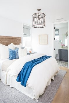 In this bedroom, the bright off-white walls and neutral furnishings get a splash of personality from the blue accents and rustic wooden headboard. Rustic Wooden Headboard, Rustic Nightstand, Glam Bedroom, Bedroom Decor, Bedroom Suites, Bedroom Rustic, Bedroom Ideas, Coastal Bedrooms, Coastal Homes