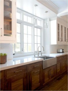 a kitchen with rustic wood cabinets and white countertops for an airy feel
