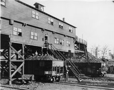 Steel railroad cars pull right under a coal tipple to be loaded the