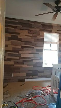 Wood accent wall. 30 panels of the untreated cedar fencing - 10 pieces stained with a gray wood stain, 10 stained with a dark gray stain and 10 were aged using a solution of a steel wool pad soaked in vinegar (for 12 hours) that we painted on. The vinegar solution gave it a beautiful finish and was faster than we thought. After we cut the pieces to the correct heights (we used 3 different heights), we used a nail gun and nailed directly into the walls, aiming for the studs. 3 hours - $60.